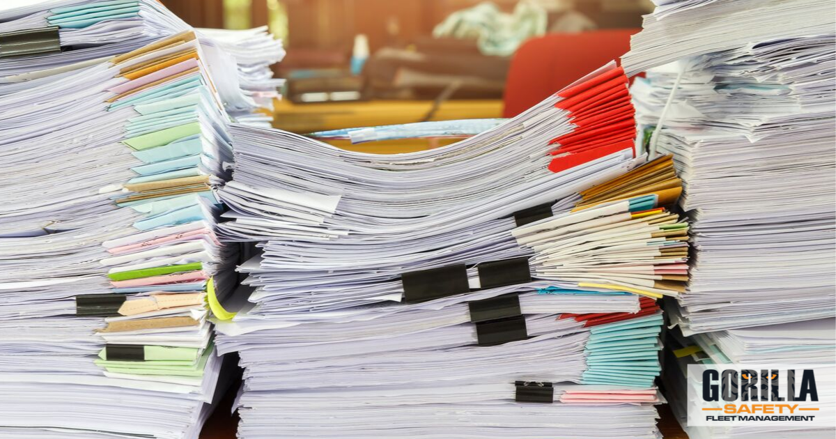 a stack of papers in need of a document management solution for fleets
