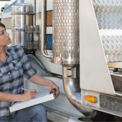 a female truck driver doing her inspection without the use of an eDVIR